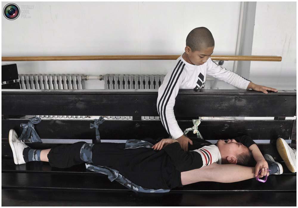Учащийся помогает своему однокласснику растягиваться во время тренировки в зале школы пекинской оперы Шэньянского университета в Шэньяне, провинция Ляонин, 3 ноября 2011 года. (REUTERS/Sheng Li)