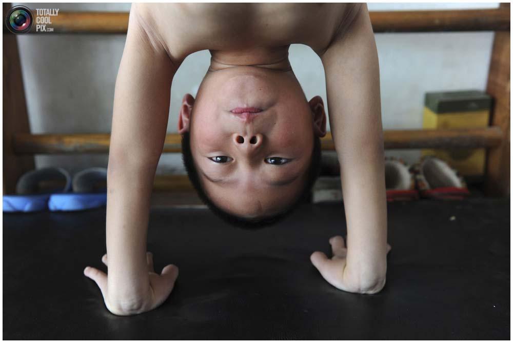 Маленький гимнаст на тренировке группы от 4 до 7 лет в городе Цзясин, провинция Чжэцзян, 10 августа 2010 года. Китайцы настаивают на новых правилах, чтобы предотвратить случаи фальсификации возраста спортсменов, из-за которого гимнастка лишилась Олимпийской медали. (REUTERS/Stringer)