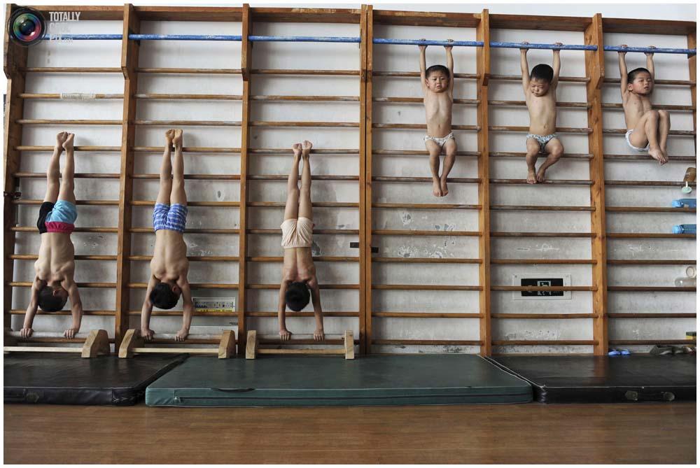 Маленькие гимнасты из группы 4-7 лет растягиваются на шведской стенке в гимнастическом зале в городе Цзясин, провинция Чжэцзян, 10 августа 2010 года. (REUTERS/Stringer)