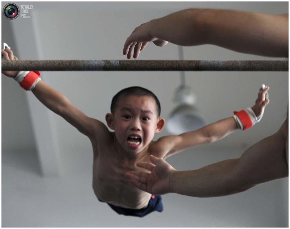 Мальчик спрыгивает с перекладины на тренировке группы 4-7 лет в гимнастическом зале в городе Цзясин, провинция Чжэцзян, 10 августа 2010 года. (REUTERS/Stringer)
