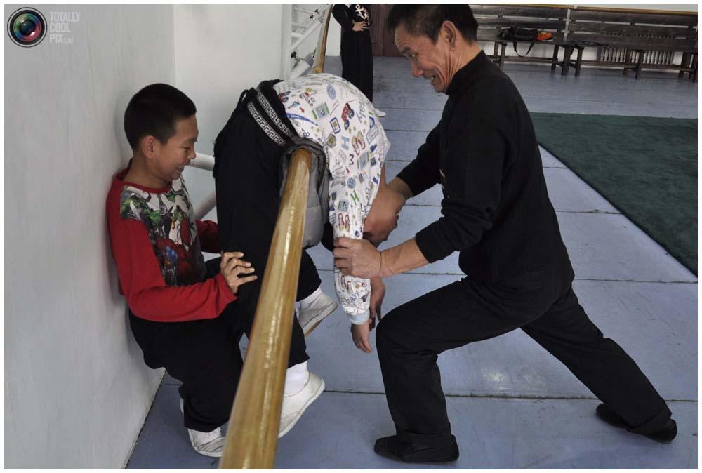 Тренер помогает мальчику растягиваться во время тренировки в зале отделения пекинской оперы Шэньянского университета в Шэньяне, провинция Ляонин, 3 ноября 2011 года. Здесь тренируется более 200 спортсменов в возрасте от 4 до 17 лет. Абитуриенты, чтобы быть допущенными к национальным вступительным экзаменам в колледжи искусств, должны тренироваться не менее 12 лет. (REUTERS/Sheng Li)
