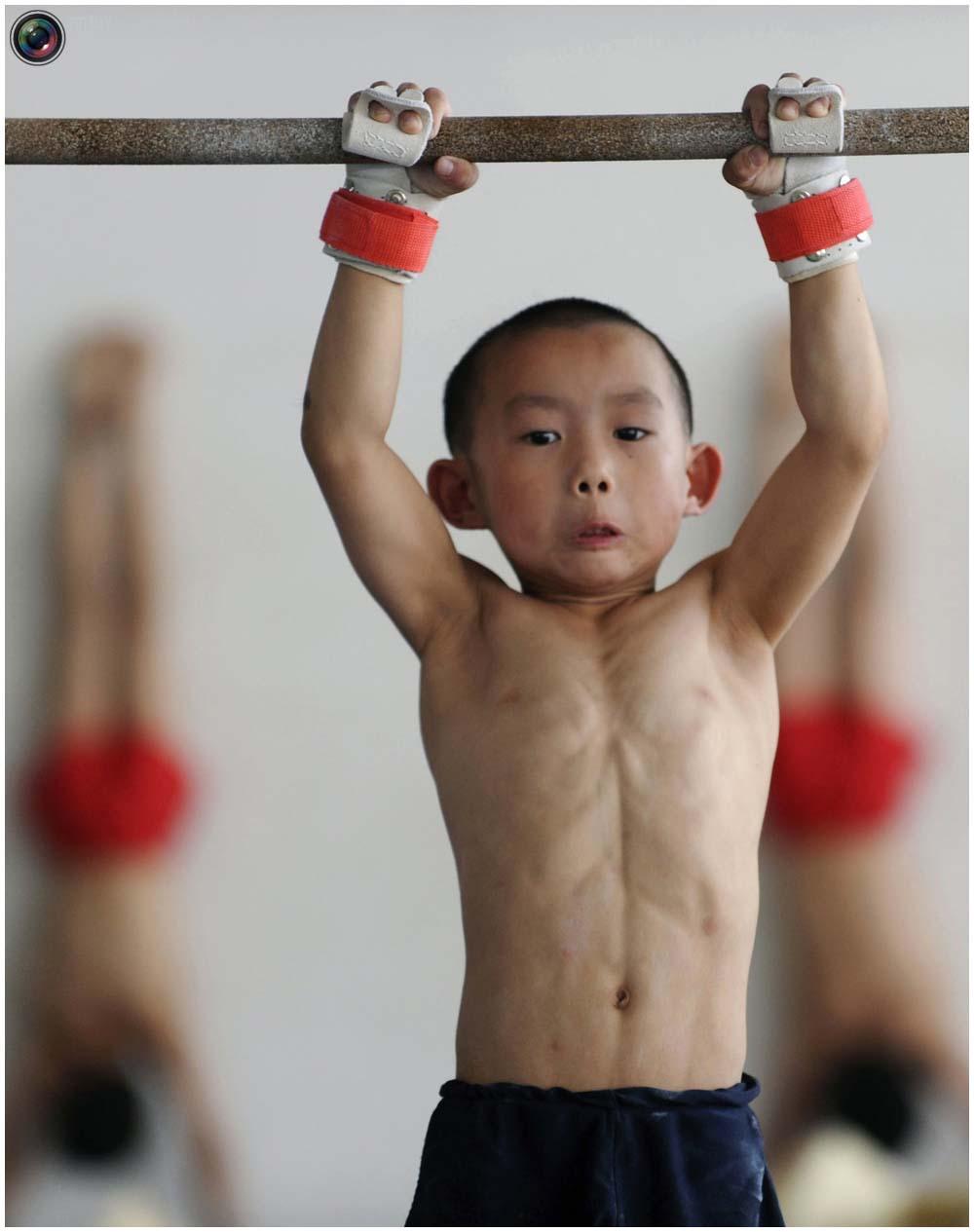 Мальчик на перекладине на тренировке группы 4-7 лет в гимнастическом зале в городе Цзясин, провинция чжэцзян, 10 августа 2010 года. (REUTERS/Stringer)