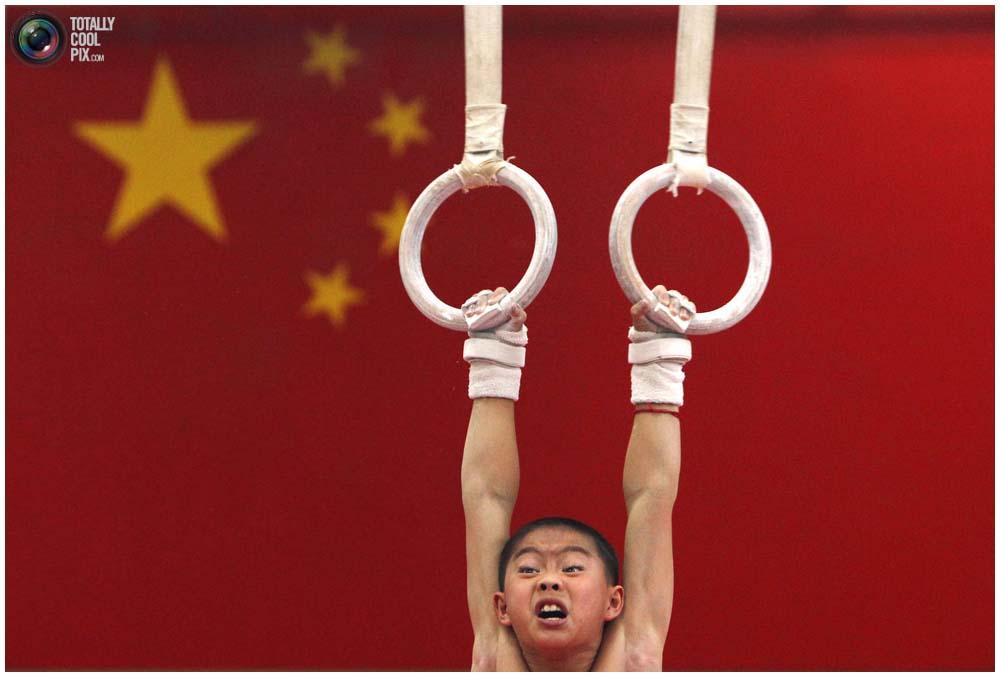 Мальчик на кольцах во время тренировки группы от 7 до 10 лет в спортивной школе Шичахай в Пекине, 18 августа 2010 года. (REUTERS/David Gray)