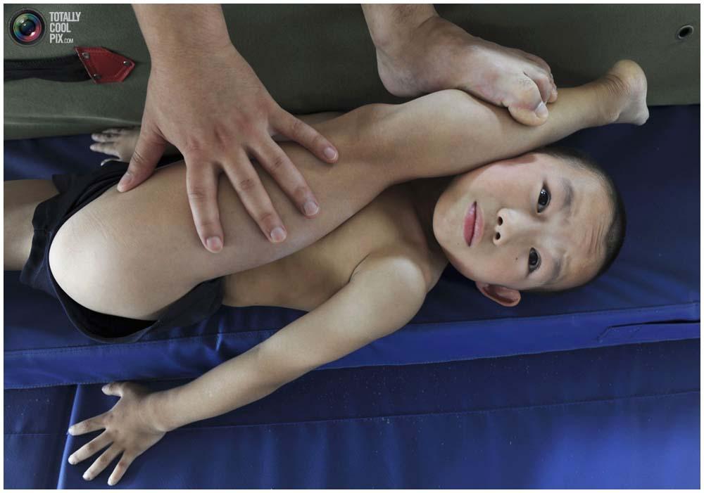 Тренер помогает растягиваться мальчику во время тренировки группы от 4 до 7 лет в городе Цзясин, провинция Чжэцзян, 10 августа 2010 года. (REUTERS/Stringer)