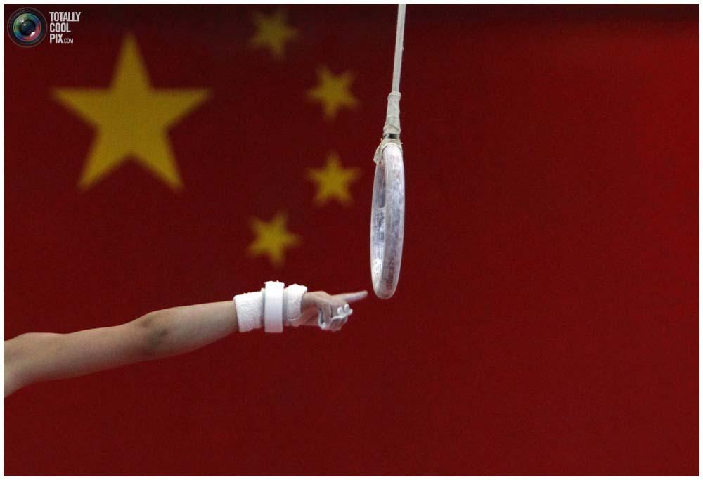 Мальчик тянется к кольцам, спортивная школа1 Шичахай в Пекине, 18 августа 2010 года. (REUTERS/David Gray)