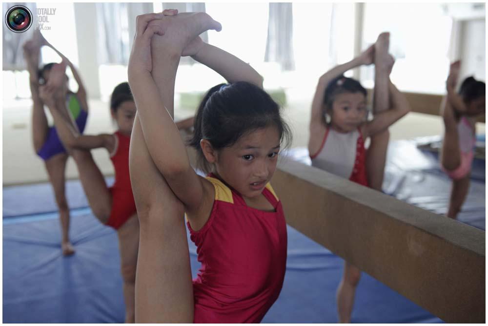 Маленькие гимнастки на тренировке группы от 4 до 7 лет в гимнастическом зале в городе Цзясин, провинция Чжэцзян, 10 августа 2010 года. Китайцы настаивают на новых правилах, чтобы предотвратить случаи фальсификации возраста спортсменов, из-за которого гимнастка лишилась Олимпийской медали. (REUTERS/Stringer)