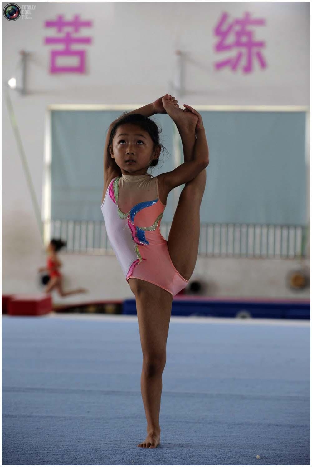 Маленькая гимнастка на тренировке группы от 4 до 7 лет в городе Цзясин, провинция Чжэцзян, 10 августа 2010 года. (REUTERS/Stringer)