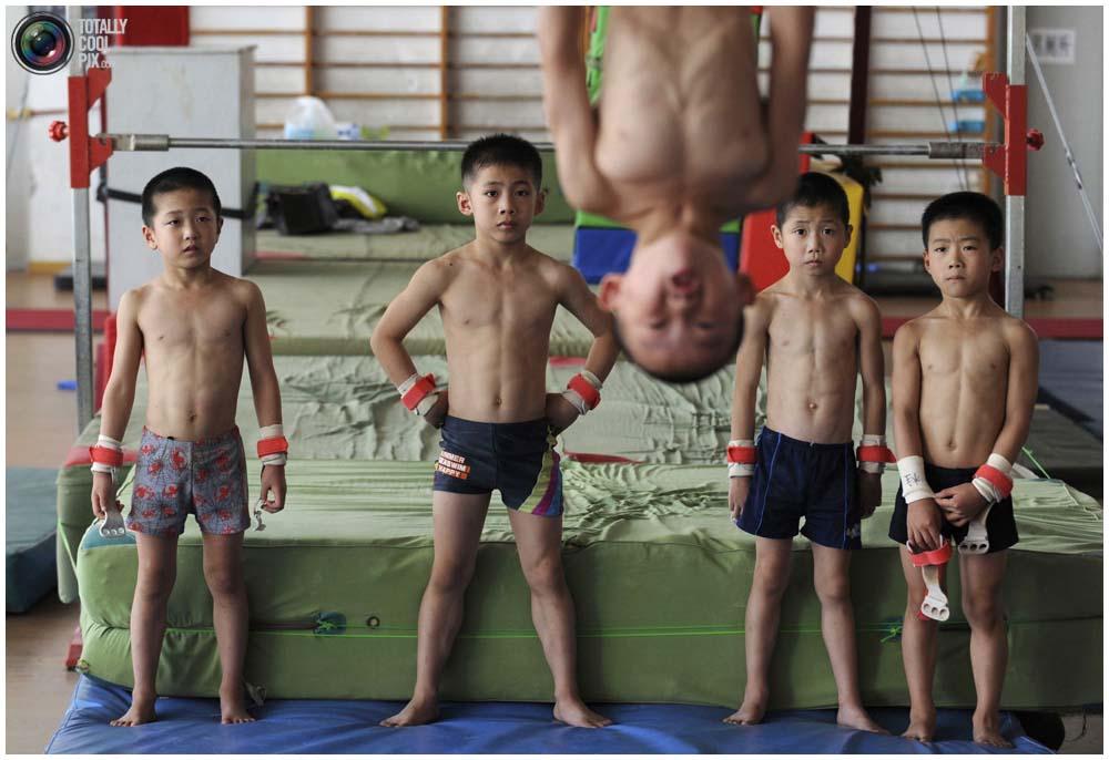 Маленькие гимнасты на тренировке группы от 4 до 7 лет в гимнастическом зале в городе Цзясин, провинция Чжэцзян, 10 августа 2010 года. (REUTERS/Stringer)
